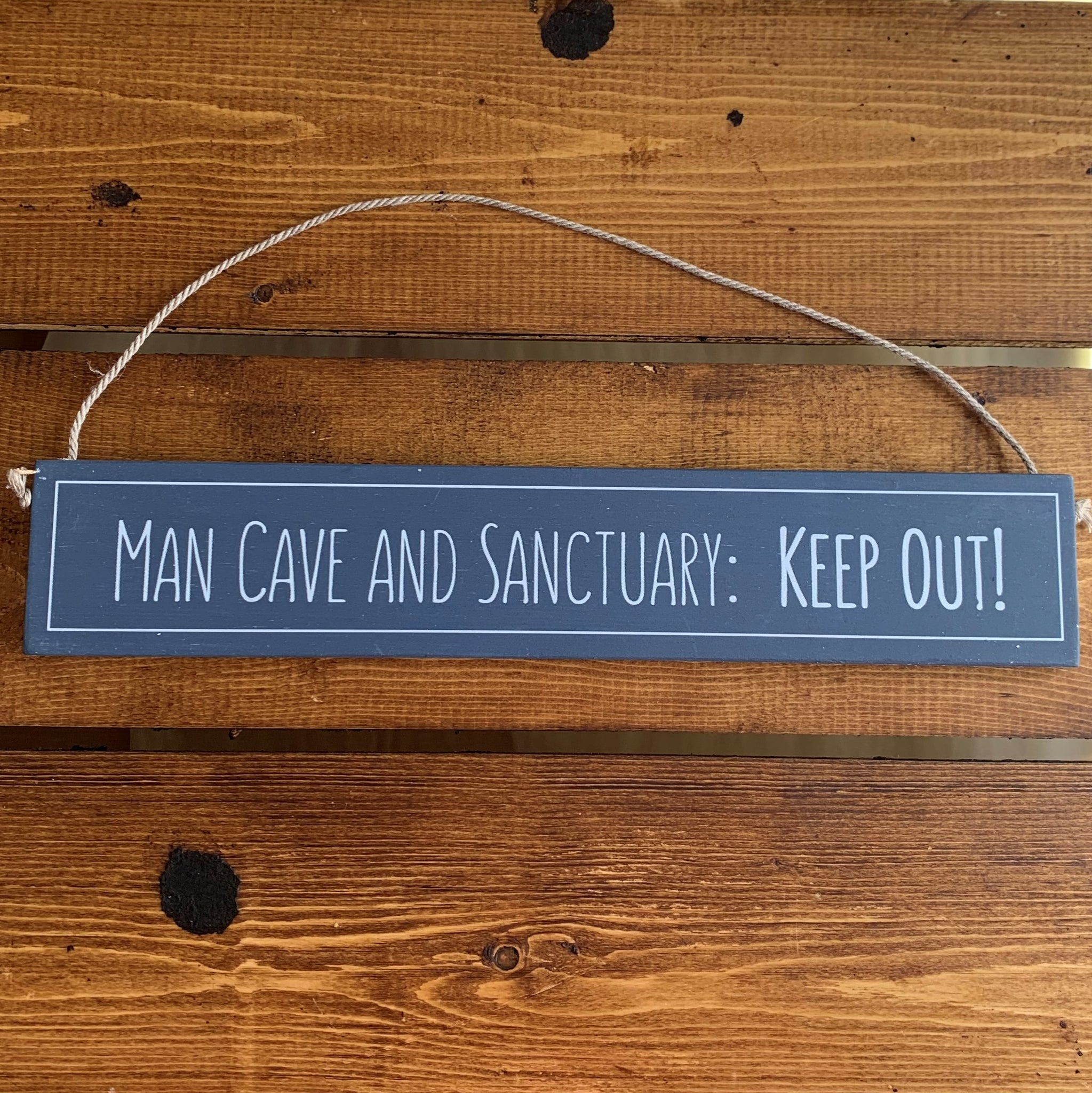 Rustic hanging wooden sign - hand painted with the printed slogan:  'Man Cave and Sanctuary: Keep Out'