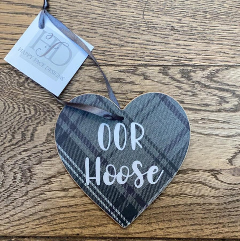 Hanging wooden heart on grey printed tartan with black ribbon and the sentiment:  'Oor Hoose'