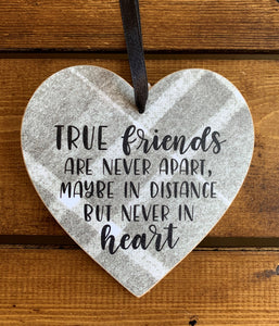 Hanging wooden heart on grey printed tartan with black ribbon and the sentiment:  'True friends are never apart, maybe in distance hut never in heart'