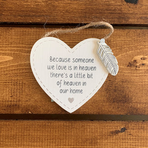 Hanging wooden heart with wooden feather and the printed sentiment:  'Because someone we love is in heaven, there's a little bit of heaven in our home'