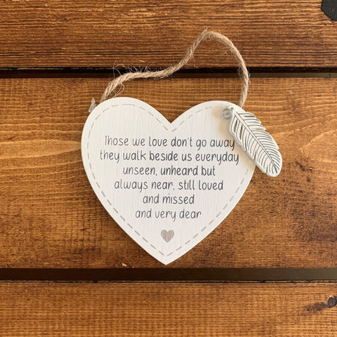 Hanging wooden heart with wooden feather and the printed sentiment:  'Those we love don't go away, they walk beside us everyday, unseen, unheard but always near, still loved and missed and very dear'
