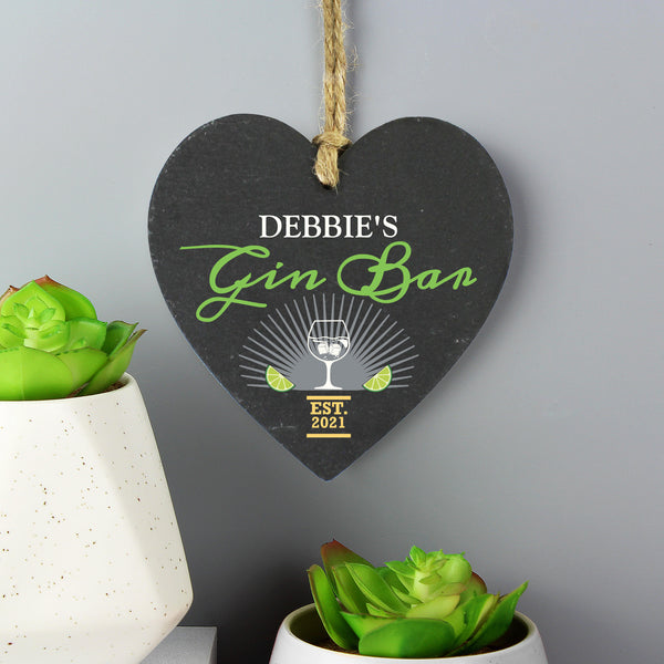 Slate hanging heart sign with natural, rustic string which can be personalised with a name of  your choice. A perfect gift for any Gin lover!  Personalise with a name up to 12 characters long (will appear in fixed upper case) and a year up to 4 characters. Gin Bar & EST is fixed text.