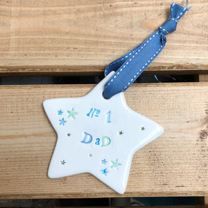 Hand painted ceramic star featuring star design and the sentiment 'No1 Dad'  Handmade in the UK using clay, glaze and paint sourced locally.  Material:  Ceramic