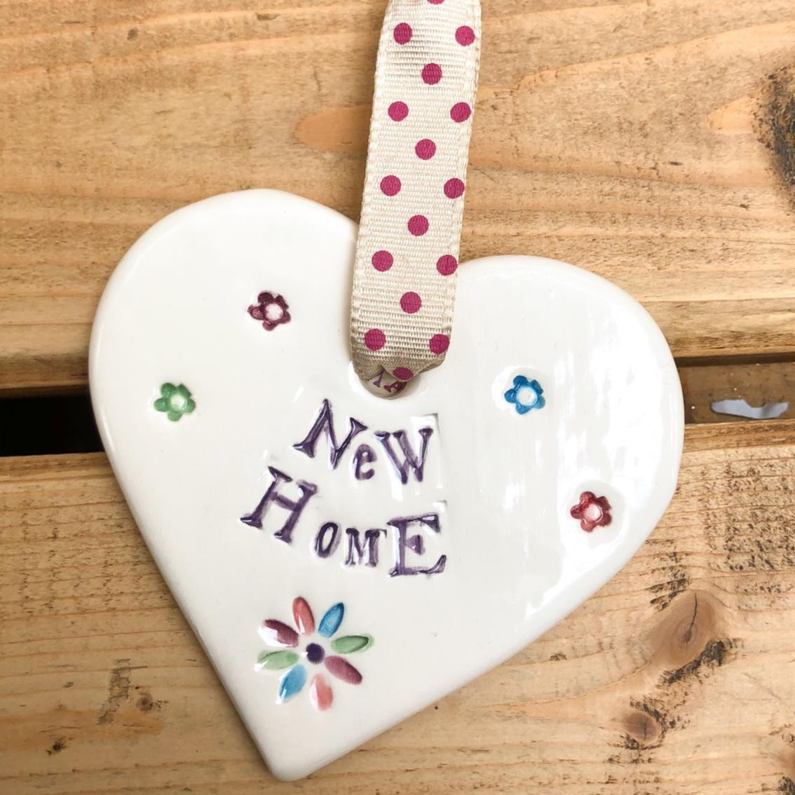 Hand painted ceramic heart featuring flower design and the sentiment 'New Home'  Handmade in the UK using clay, glaze and paint sourced locally.  Material:  Ceramic