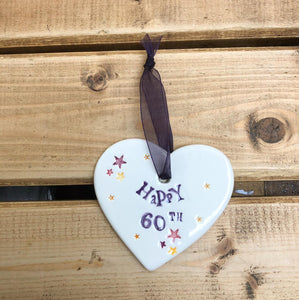 Hand painted ceramic heart featuring star design and the sentiment 'Happy 60th' Handmade in the UK using clay, glaze and paint sourced locally. Material: Ceramic