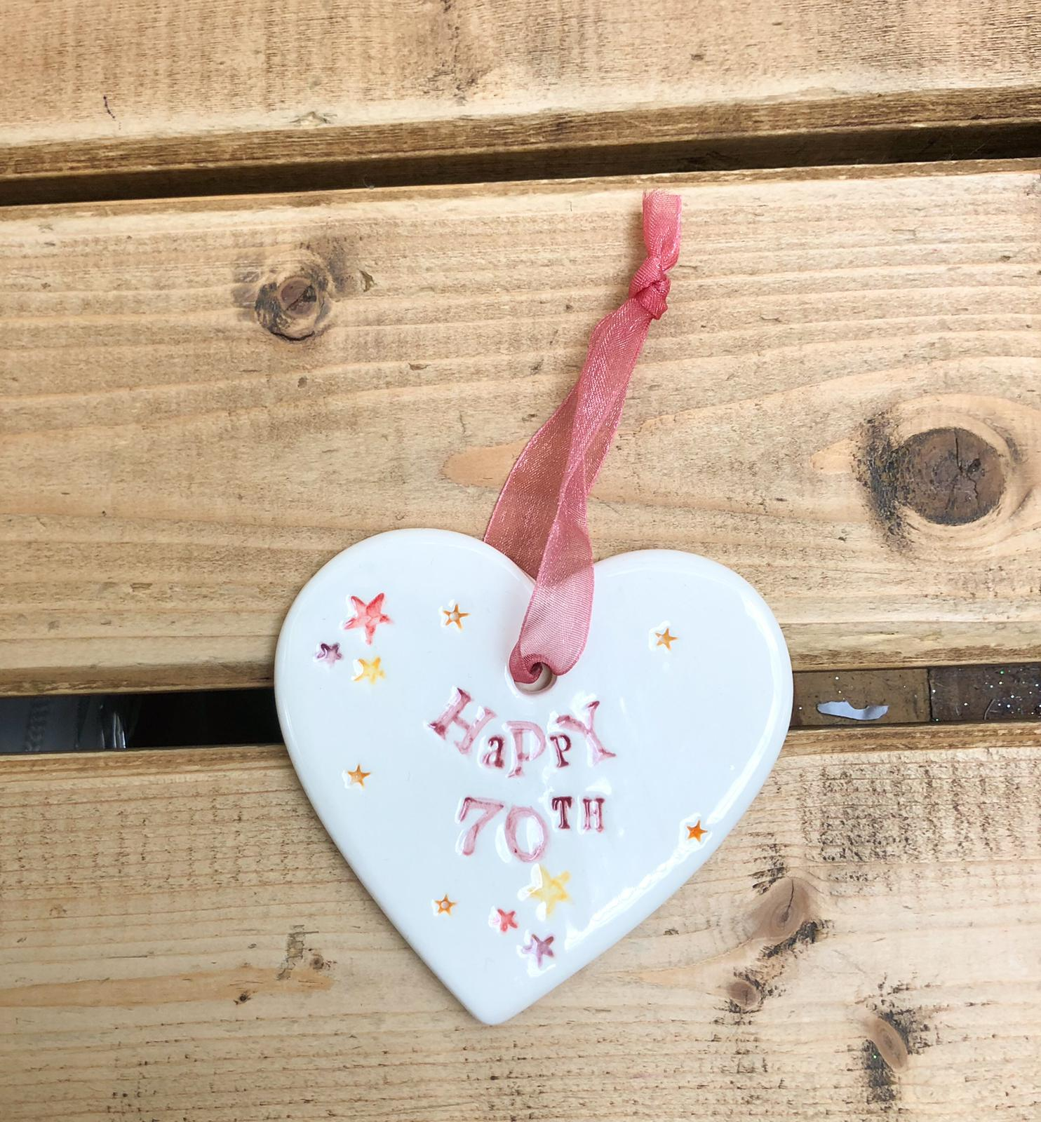 Hand painted ceramic heart featuring star design and the sentiment 'Happy 70th' Handmade in the UK using clay, glaze and paint sourced locally. Material: Ceramic
