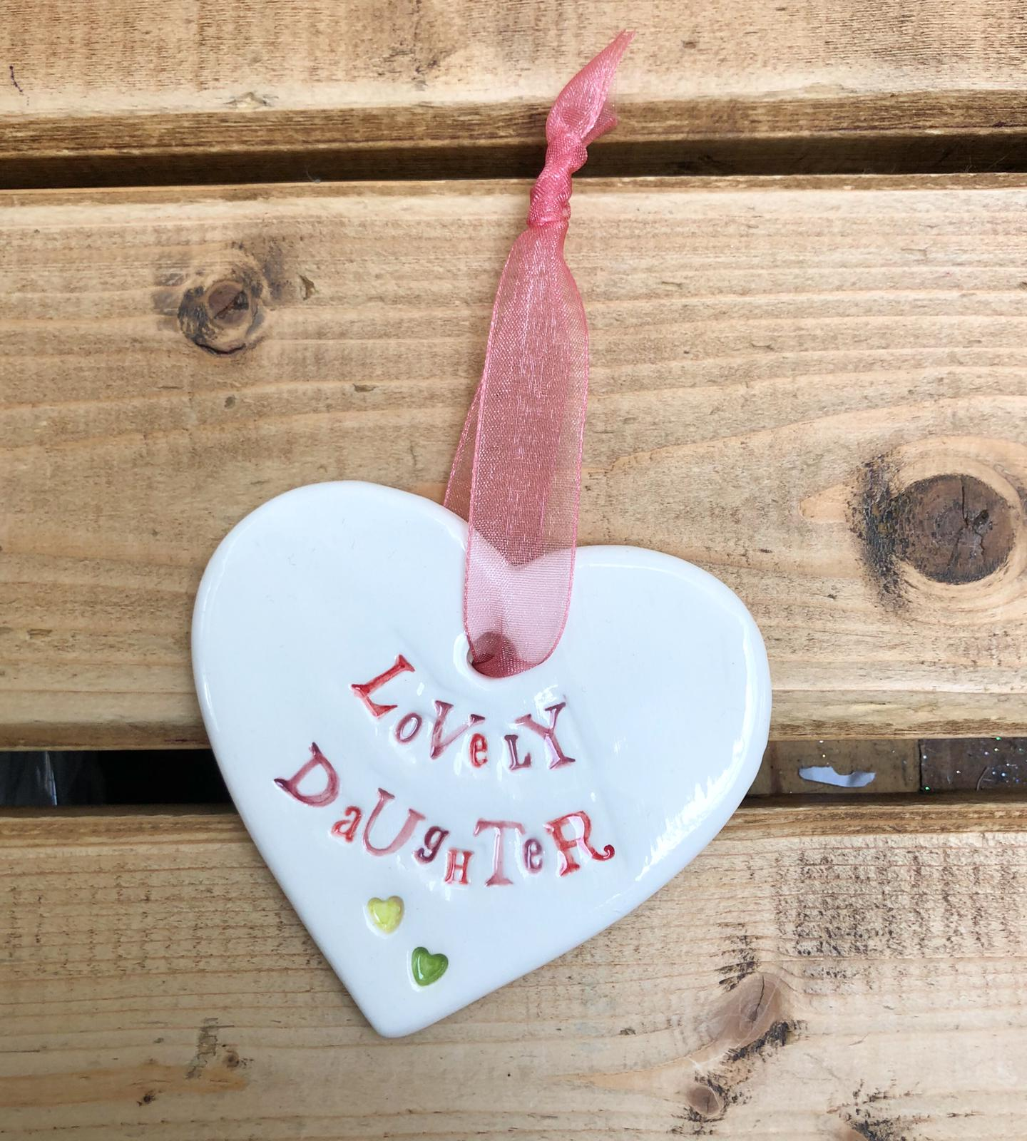 Hand painted ceramic heart featuring a flower design and the sentiment 'Lovely Daughter' Handmade in the UK using clay, glaze and paint sourced locally. Material: Ceramic