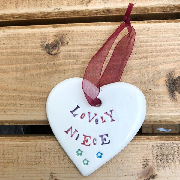Hand painted ceramic heart featuring a flower design and the sentiment 'Lovely Niece'  Handmade in the UK using clay, glaze and paint sourced locally.  Material:  Ceramic