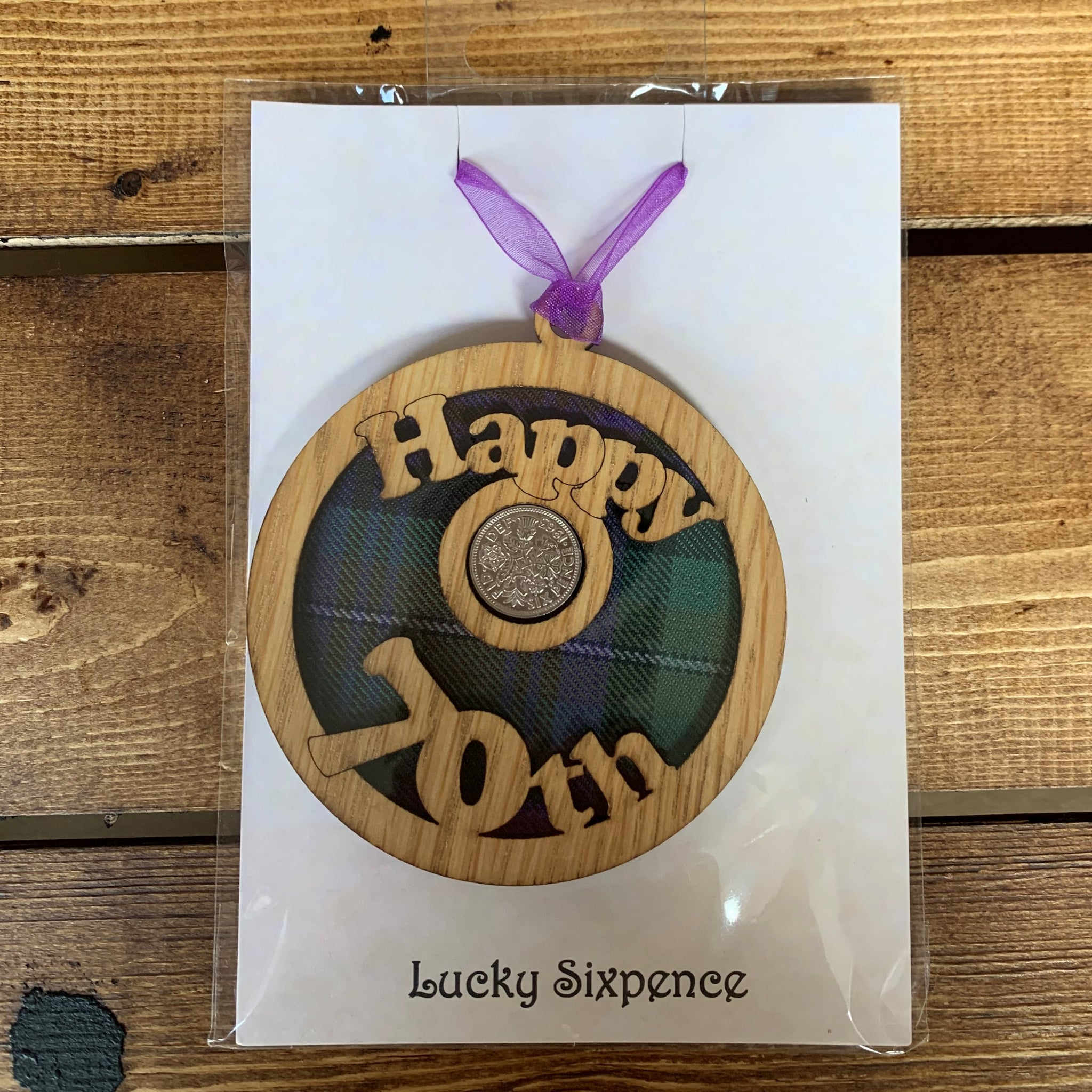 A unique keepsake gift with a Scottish twist.  The sixpence is mounted onto a round hanging oak veneered wood with tartan inserts, mounted on card and packaged in clear cellophane packets.  'Happy 70th' is cut into the wooden hanging.