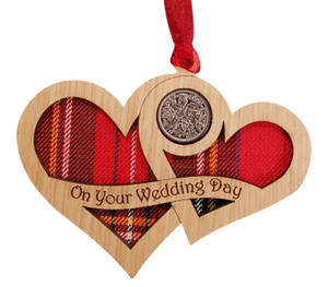 A unique keepsake gift with a Scottish twist.  The sixpence is mounted onto hanging oak veneered wooden interlocking hearts with tartan inserts, mounted on card and packaged in clear cellophane packets.  The sentiment 'On your Wedding Day' is engraved across the hearts.
