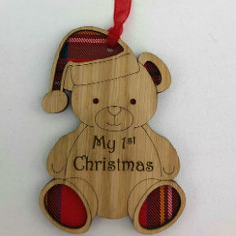 A unique keepsake 1st Christmas decoration with a Scottish twist.  A wooden Teddy Bear with tartan inserts and cute santa hat, with sweet sentiment which reads 'My 1st Christmas', mounted on card and packaged in clear cellophane packets.