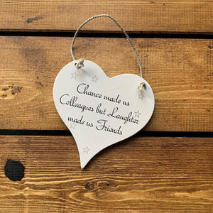 Hanging wooden heart - hand painted with the printed slogan:  'Chance made us colleagues but laughter made us friends'