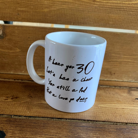 Monochrome Mug with '30' on one side and a cheeky Scottish slang poem on the reverse which reads:  'A hear yer 30, lets hae a cheer, yer still a fud but a love ye dear'