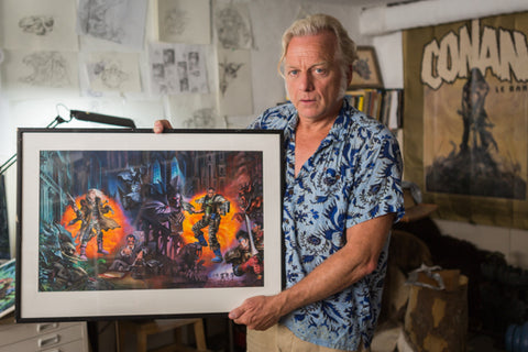 Paul Bonner holding painting in a loud shirt