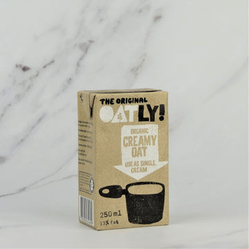 250ml carton of Oatly Organic Oat Cream on a white marble background