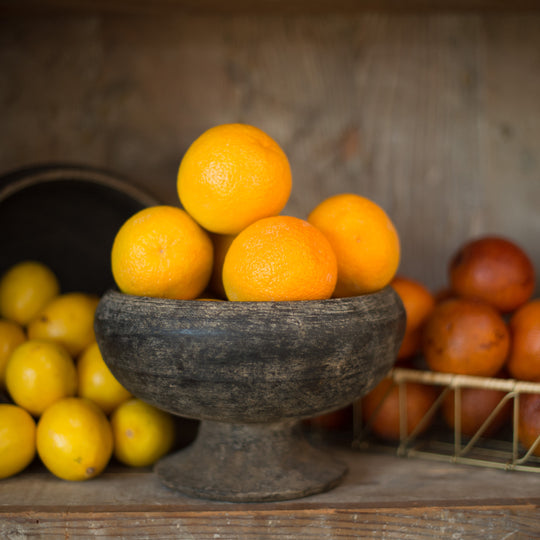 Bowl of Oranges with Tomatoes Behind it