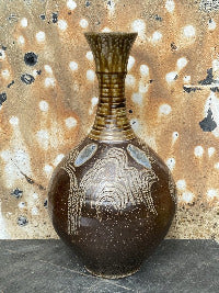 Long necked vase with combing through a kaolin slip glaze with blue glass runs and an ash glaze neck