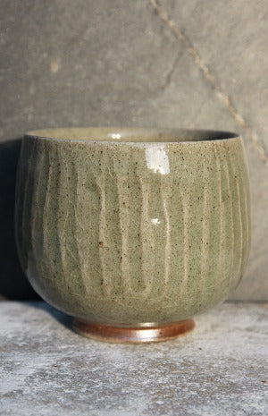 Tea bowl with incised vertical lines under green celadon glaze.