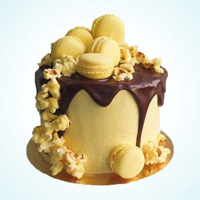 Yellow Drip Cake with Popcorn and Macarons