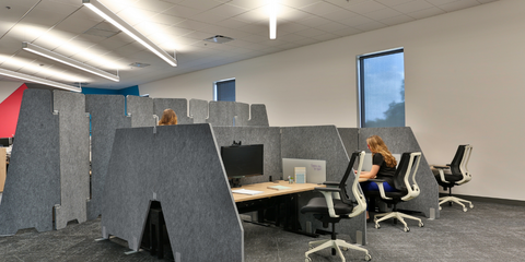 2 women working at desks with gray PET wing dividers