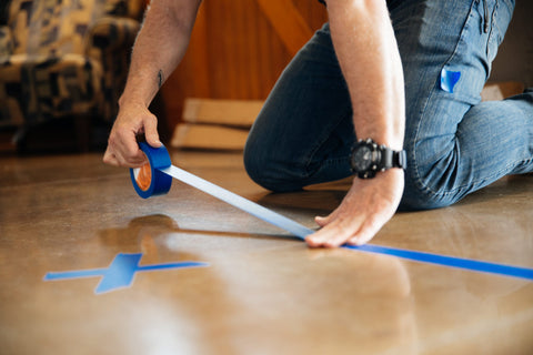 Man putting blue tape on the ground in an X and a line