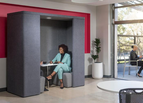 Woman smiling while in discussion with coworker sitting in gray 2-person pod