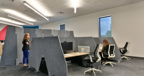 two women at workstations with PET wing dividers and a room divider in the background