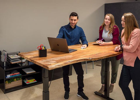 3 colleagues discussing a project at a laptop on a Live Edge height-adjustable desk