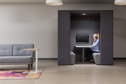 Woman sitting working alone in a gray pod