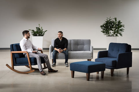 2 men sitting in gray and navy lounge furniture and having a conversation