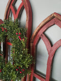 Side view of the red cathedral windows with holly berry wreath.