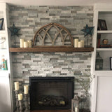 Gray half moon window on mantle with candles over fireplace.