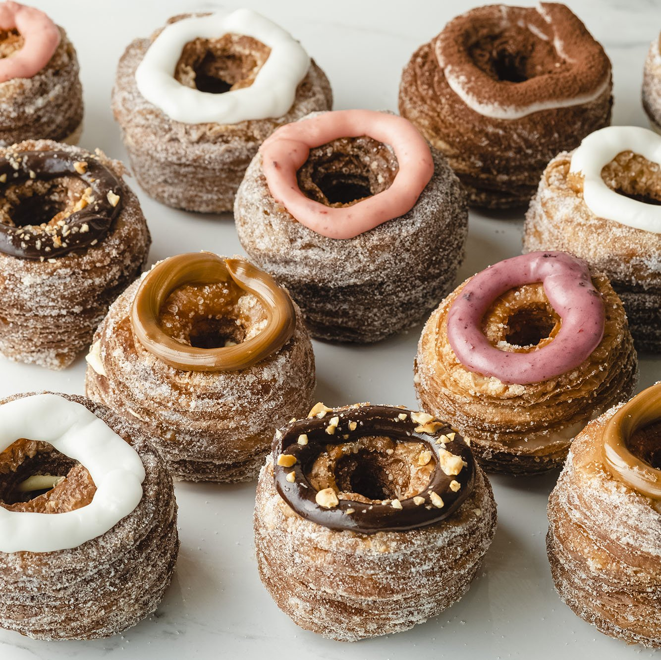 Set of assorted cronut dessert pastry topped with dulce de leche, tiramisu, vanilla, strawberry, hazelnut, and mixed berry icing.