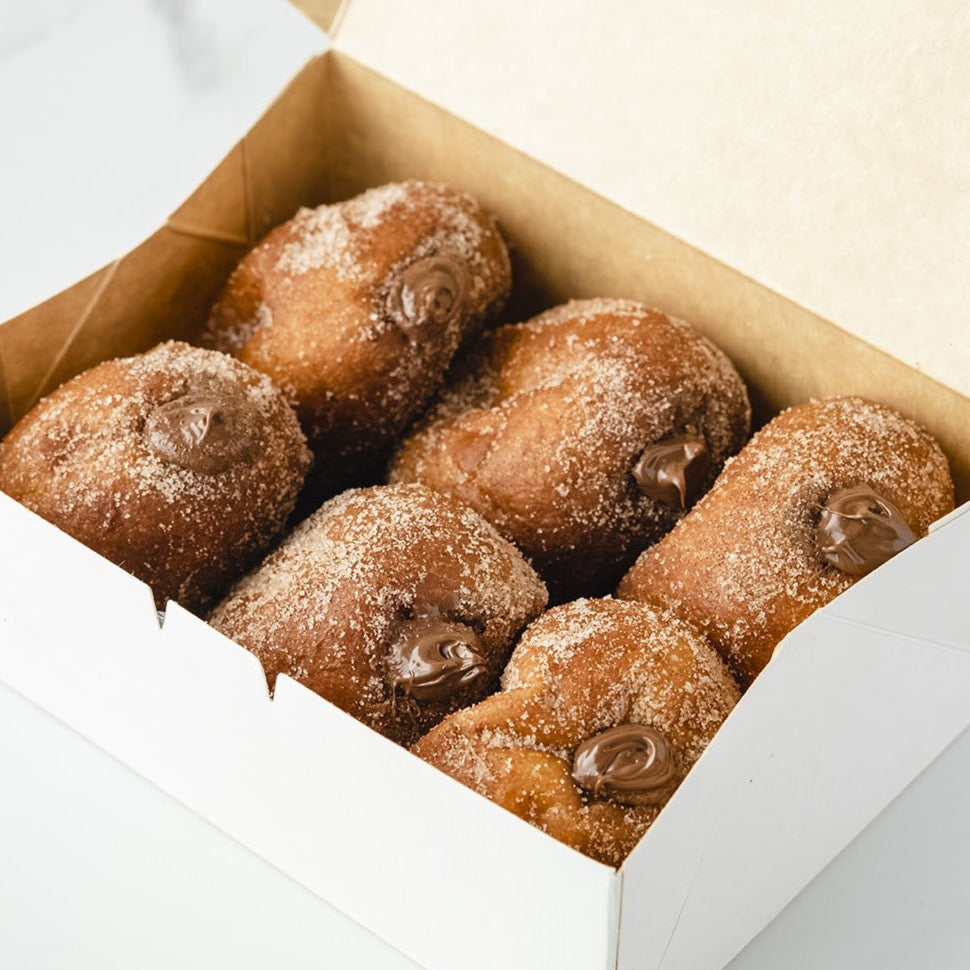 Box of Hazelnut stuffed Bomboloni dessert pastry.