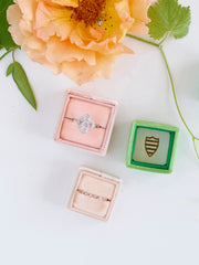 pink, green, and nude velvet ring boxes