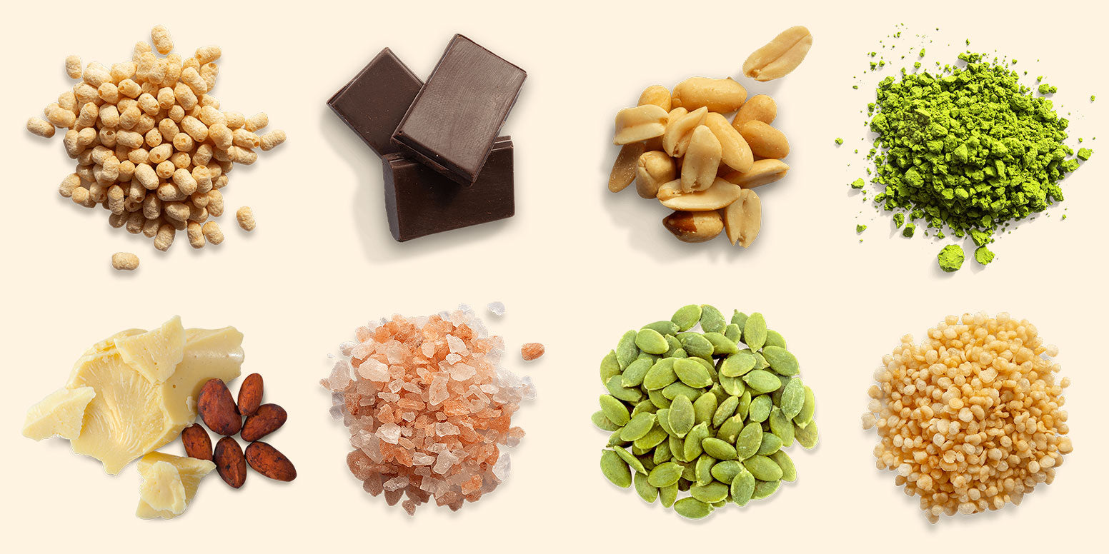 Assortment of product ingredients: pea protein, chocolate, peanuts, Japanese matcha, cocoa butter, pink salt, pumpkin seeds, and quinoa.