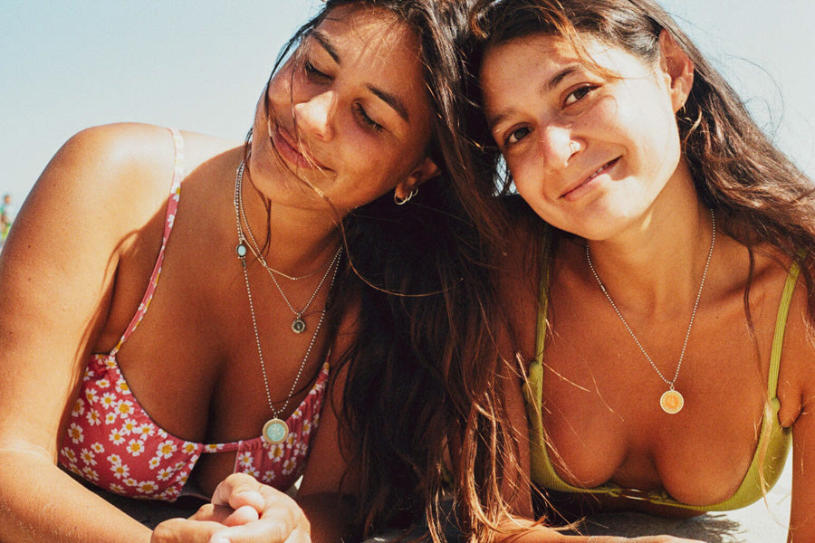 two girls on the beach with best friend necklaces