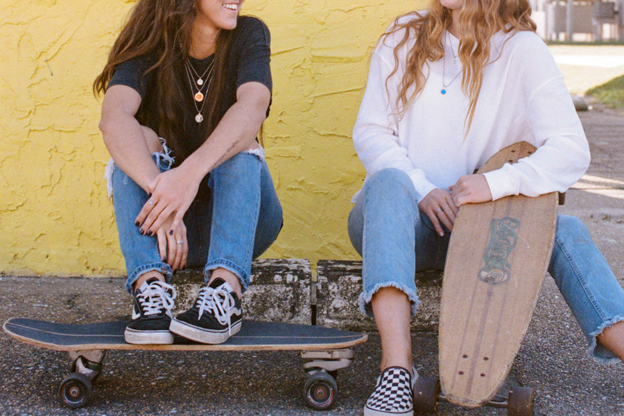 two girls with skateboards wearing best friends necklaces