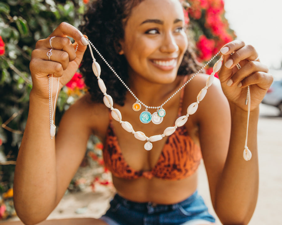 girl holding shell necklace and st christopher necklaces