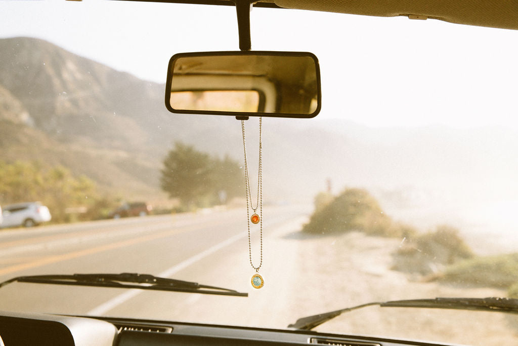 st christopher surf necklaces hanging on rear view mirror in vw bus