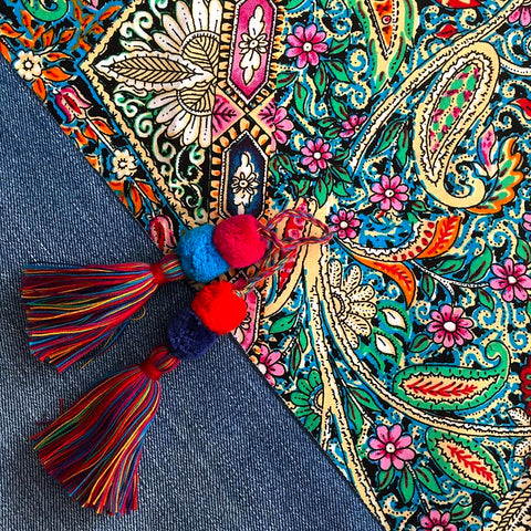 Brightly colored paisley material alongside denim with tassels laid over the top
