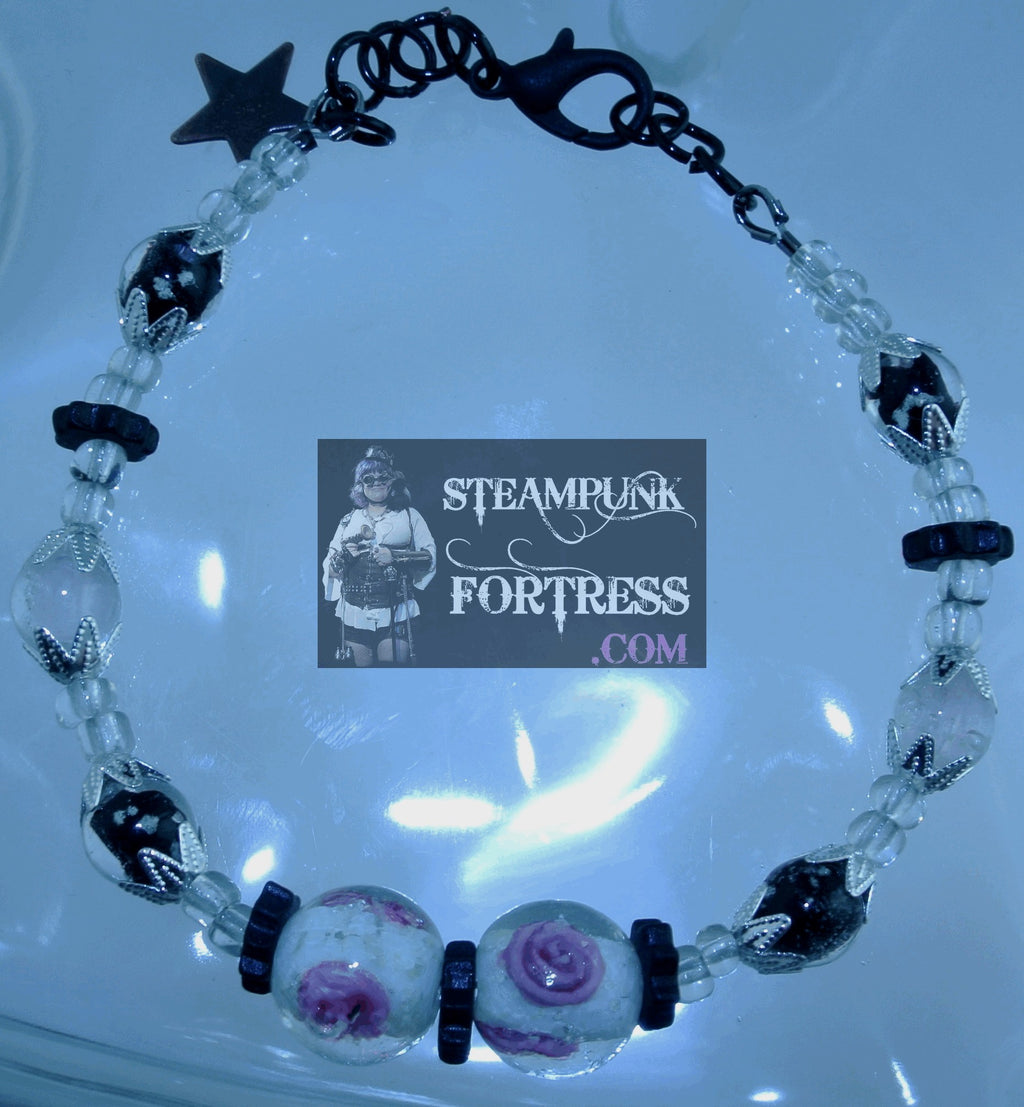 GLOW IN THE DARK CLEAR BEADS WHITE PINK GLOW ROSES WHITE PINK BLACK GLOW BEADS BLACK CERAMIC GEARS SILVER BEAD CAPS GLOW IN THE DARK WIRE BRACELET SET AVAILABLE STARR WILDE STEAMPUNK FORTRESS