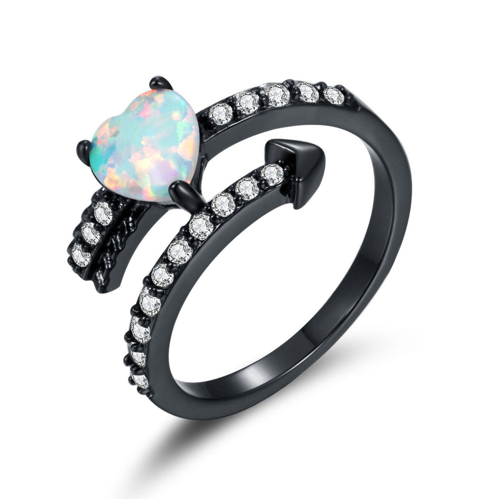 A heart-shaped opal ring inlaid with black and gold zircons