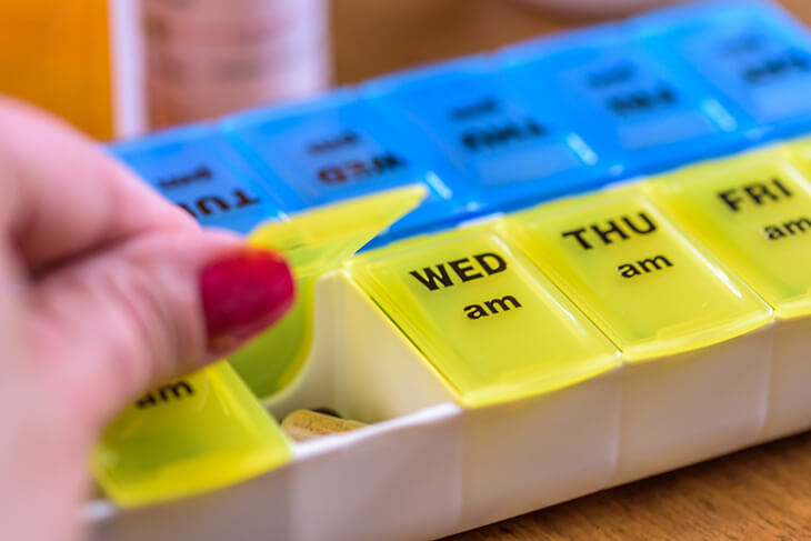 person opening medication management tray