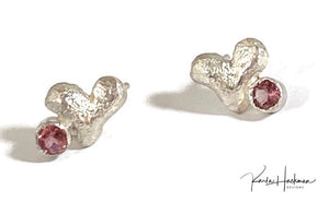 These  hand-carved petite, lilting hearts are carved in wax and cast in sterling silver, and then they are given a bright hammered finish and adorned with a 3mm gemstone in red garnet or pink tourmaline.
