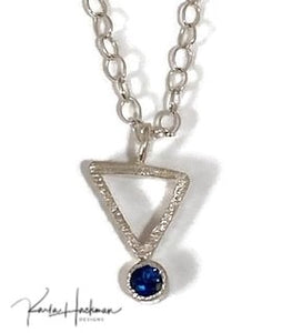 Petite sterling silver triangle pendant hangs from a delicate link chain in sterling silver. Pendant is given a hammered texture and a bright finish and is adorned with a 4mm gemstone, topaz or garnet.