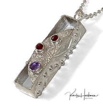 Load image into Gallery viewer, A hollow tapered rectangle is carved in wax and cast in sterling silver and is decorated on 3 sides. Front facing panel has a hammered texture and 3 rose cut gemstones, two garnets and one amethyst.