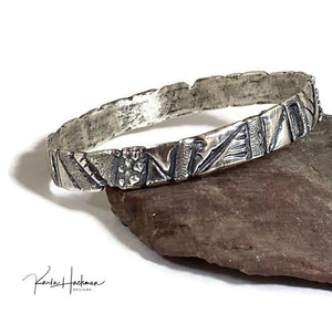 Hand carved in wax and cast in sterling silver, this bangle is a mix of geometric and freeform designs.  Once cast, the piece is given additional texture and an oxidized finish.