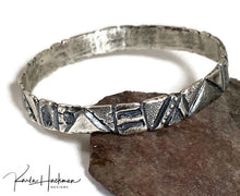 Load image into Gallery viewer, Hand carved in wax and cast in sterling silver, this bangle is a mix of geometric and freeform designs. Once cast, the piece is given additional texture and an oxidized finish.