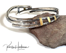 Load image into Gallery viewer, Hand-fabricated and one-of-a-kind, this mixed metal organic bangle in sterling silver and 18 karat gold looks great stacked with other jewelry or worn alone on the wrist. Bracelet is hammer textured with mutliple textures, both faceted and more organic patterns, and given an oxidized finish.